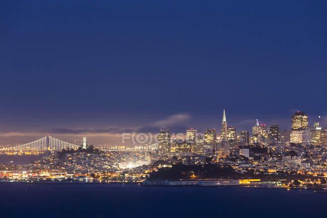Estados Unidos, California, San Francisco, horizonte y Oakland Bay Bridge en la hora azul - foto de stock