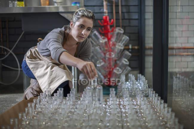 Молодая женщина, сортировка стеклянные бутылки — стоковое фото