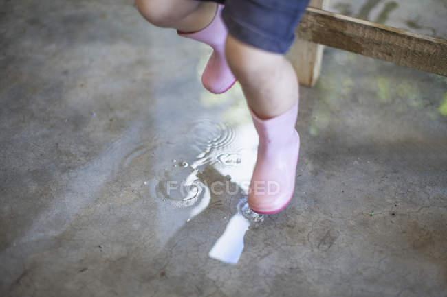 Petite fille en Roses bottes en caoutchouc sauter dans une flaque d'eau, vue en coupe de basse — Photo de stock