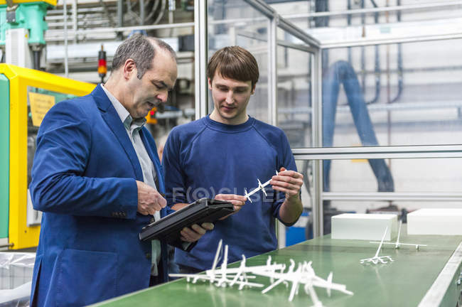 Manager and worker doing quality assessment in plastics factory — Stock Photo