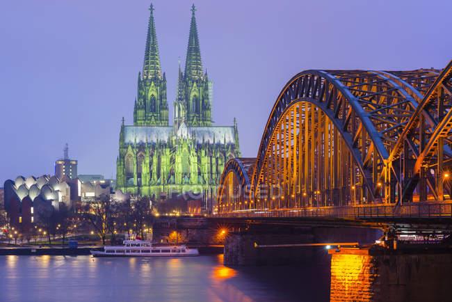 Alemania, Colonia, vista a la Catedral de Colonia iluminada con el puente Hohenzollern en primer plano - foto de stock