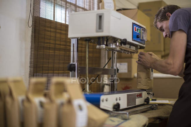 Человек, работающий на упаковке кофейных бобов вакуумный герметик — стоковое фото