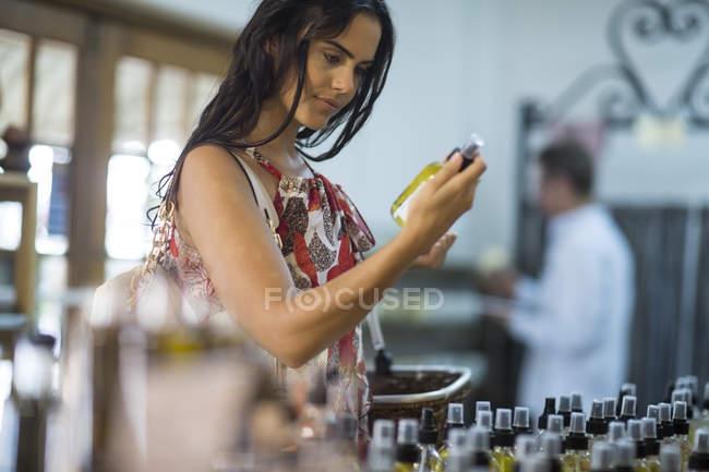 Женщина держит бутылку аромата в магазине — стоковое фото