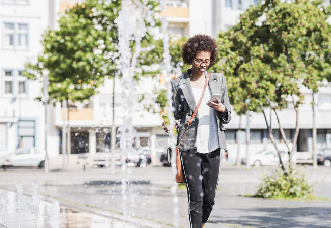 Smiling woman looking at her smartphone — Stock Photo