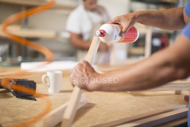 Человек, нанесения клея на раме в мастерской холст — стоковое фото