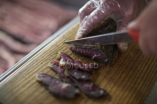 Butcher cutting biltong on wooden board — Stock Photo