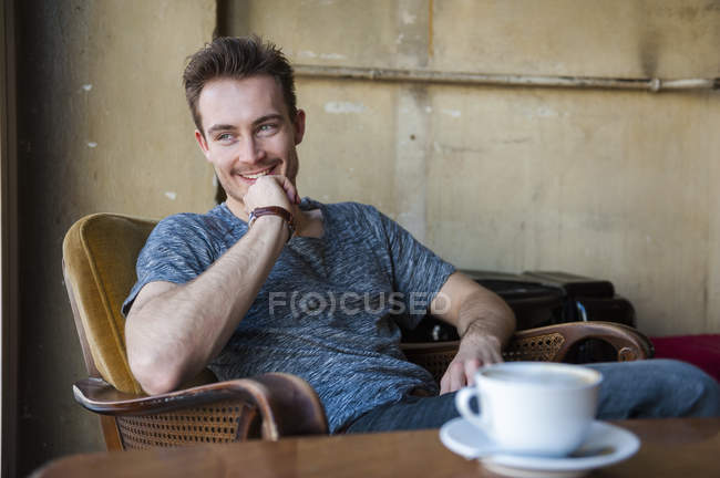 Portrait of happy young man sitting in a coffee shop — Stock Photo