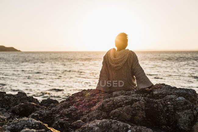 Woman sitting on rock at beach and enjoying sunset — Stock Photo
