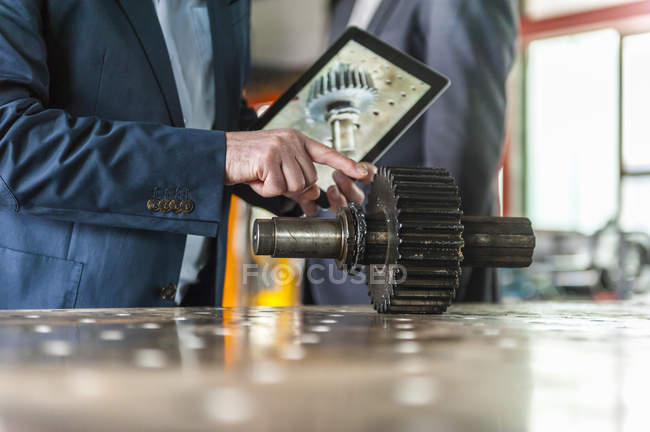 Engineers with digital tablet and gear drive — Stock Photo