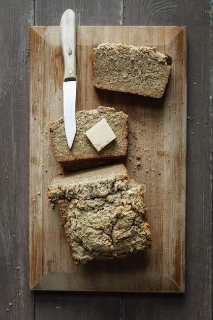 Pan de trigo sarraceno sin gluten casero, pedazo de mantequilla y cocina cuchillo tablero de madera - foto de stock