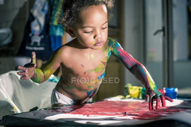 Girl drawing  red picture with fingercolors and is fully smeared of colors — Stock Photo
