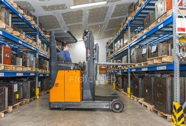 Chariot élévateur de conduite d'entrepôt dans le stockage pour des blocs de machine — Photo de stock