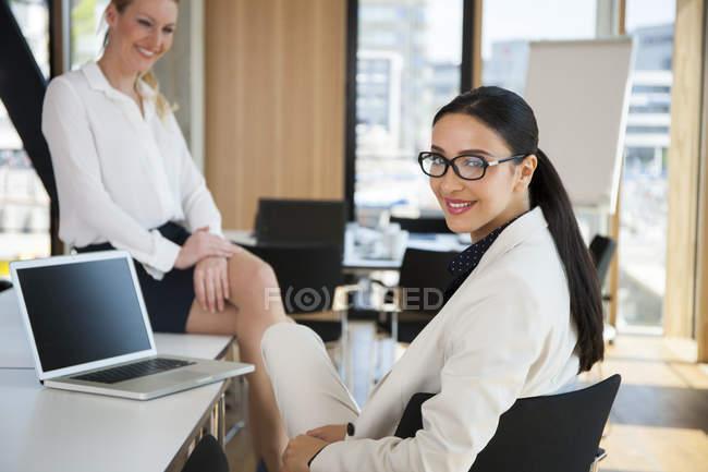 Deux femmes d'affaires souriantes en fonction — Photo de stock
