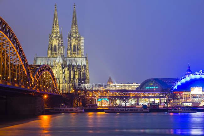 Allemagne, Cologne, vue sur la cathédrale de Cologne éclairée avec pont Hohenzollern au premier plan — Photo de stock