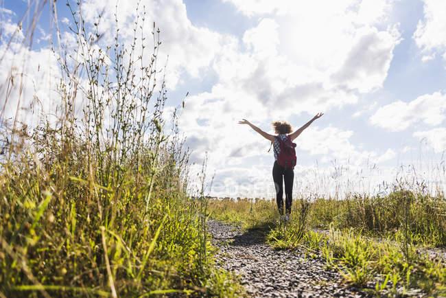 Jeune femme enthousiaste sur le chemin du champ — Photo de stock