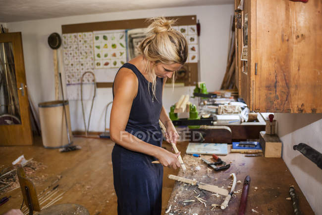 Woman in workshop working on stone age spear thrower — Stock Photo