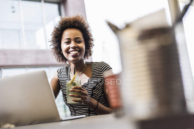 Portrait of smiling woman with beverage in sidewalk cafe — Stock Photo