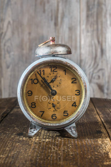 Closeup of vintage alarm clock placed on table, wooden wall background — Stock Photo