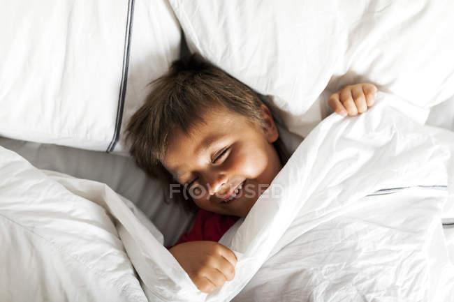 Garotinho sorridente deitado na cama tentando dormir — Fotografia de Stock
