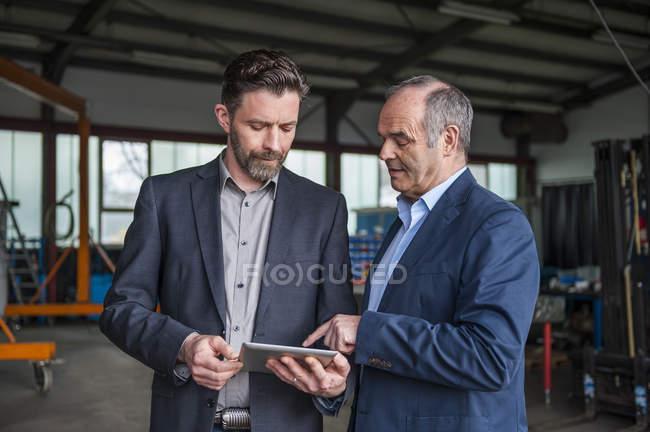Инженеры с цифровым планшетом в мастерской — стоковое фото