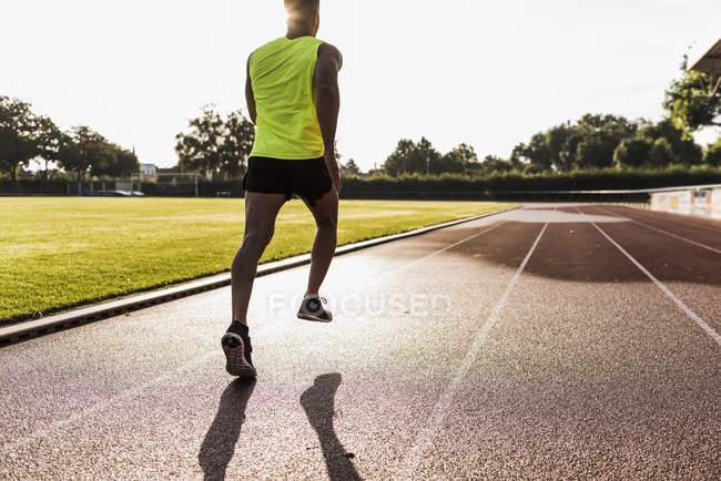 Young sporty caucasian man running on tartan track — Stock Photo