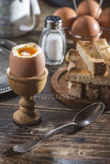 Gekochte Eier, Toast, Salz und Löffel auf Holztisch — Stockfoto