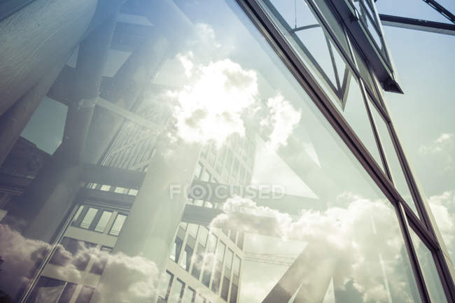 Glass facade with reflected buildings and clouds — Stock Photo