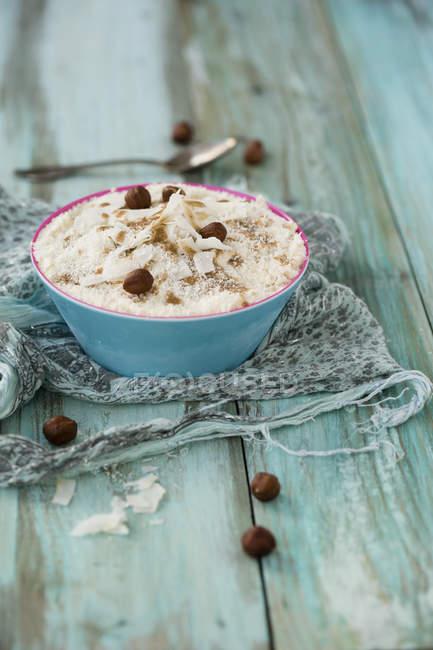 Bowl of coconut ice cream with hazelnut mush and hazelnuts — Stock Photo