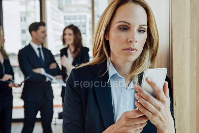 Empresária no escritório olhando para o telefone celular com empresários em segundo plano — Fotografia de Stock