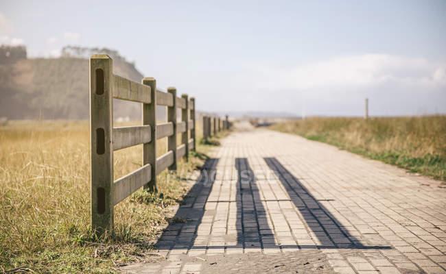 Испания, Астурия, Деревянный забор и тень над пустой набережной — стоковое фото