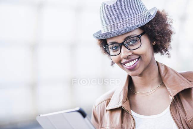 Retrato de uma jovem sorridente usando chapéu e óculos — Fotografia de Stock