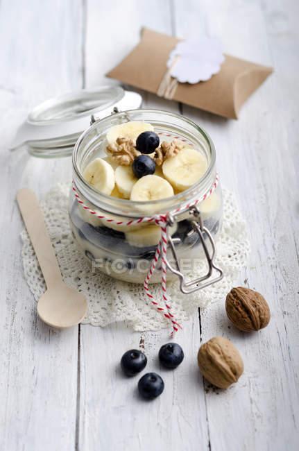 Preservando o pote de flocos de aveia regada, fatias de banana, mirtilos e nozes — Fotografia de Stock