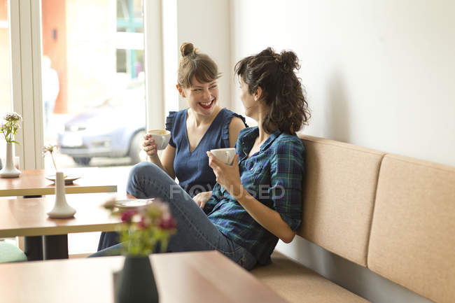 Two happy friends in a coffee shop — Stock Photo