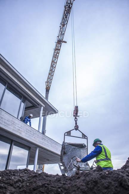 Operaio edile in cantiere con gru — Foto stock