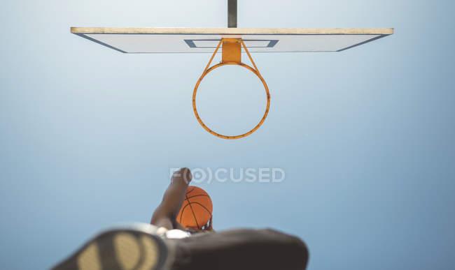 Молодой человек, нацеленный на баскетбольное кольцо — стоковое фото
