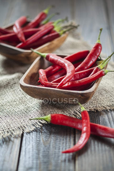 Wooden bowl of red chili peppers on jute and wood — Stock Photo