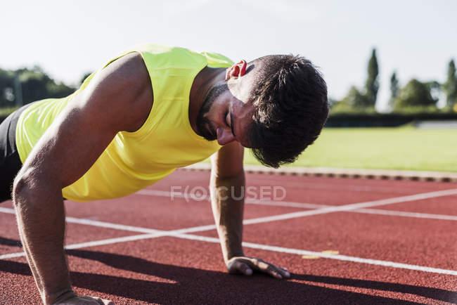 Спортсмен, делая pushu-ups на тартан трек — стоковое фото