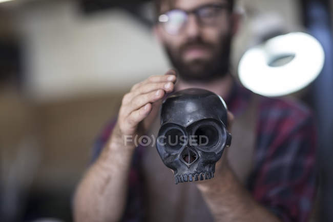 Artist holding skull sculpture in art studio — Stock Photo