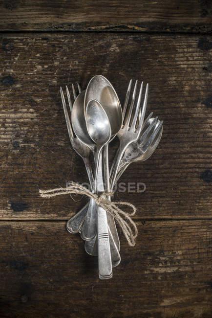 Velhos garfos e colheres amarrados com corda — Fotografia de Stock