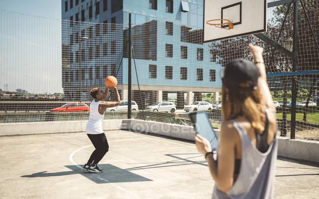 Молодая женщина с цифровым планшетом разговаривает с баскетболистом — стоковое фото