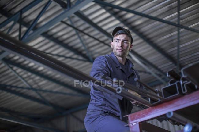 Meccanico in officina che preleva barre di acciaio da scaffali alti — Foto stock