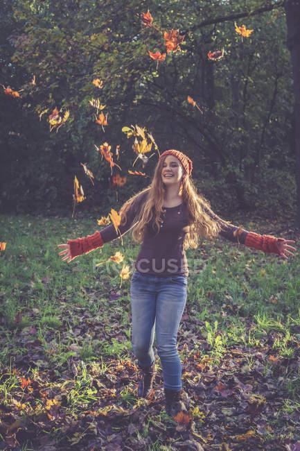Дівчинка-підліток кидали осені листя — стокове фото