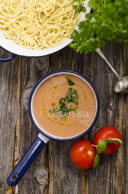 Pot of pasta, saucepan of tomato sauce, tomatoes and basil leaves on wood — Stock Photo