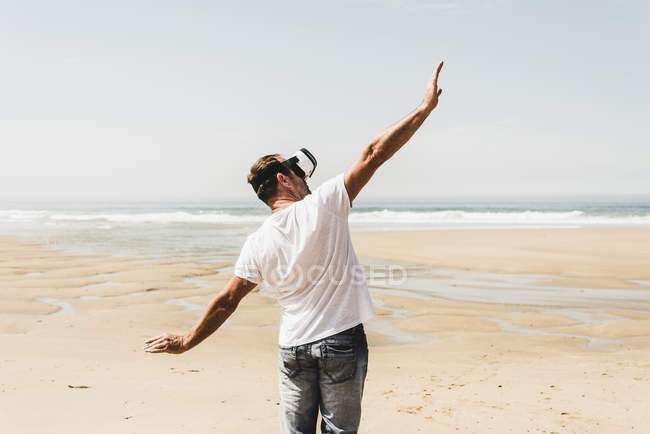 Mature man standing on the beach wearing VR glasses — Stock Photo