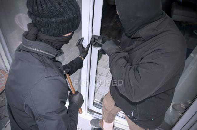 Deux cambrioleurs ouvrant la porte terrasse de la maison avec marteau et pied-de-biche — Photo de stock
