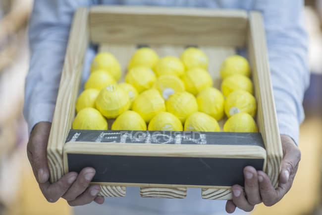 Close-up of Man holding crate of fresh lemons — Stock Photo