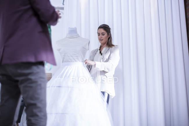 Портниха с свадебное платье — стоковое фото