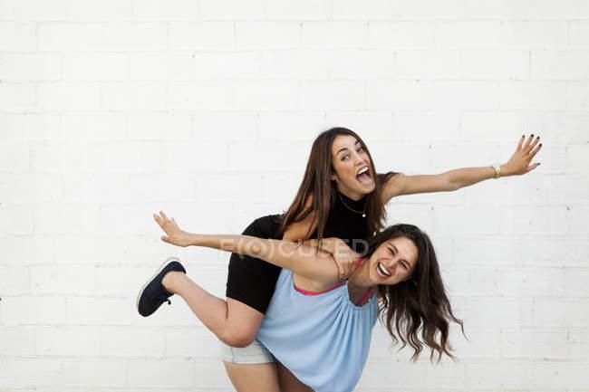 Rindo mulher dando seu melhor amigo um passeio de piggyback na frente da parede branca — Fotografia de Stock