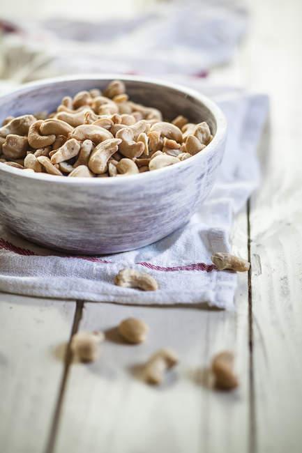 Taza de anacardos tostados y salados en toalla de cocina - foto de stock