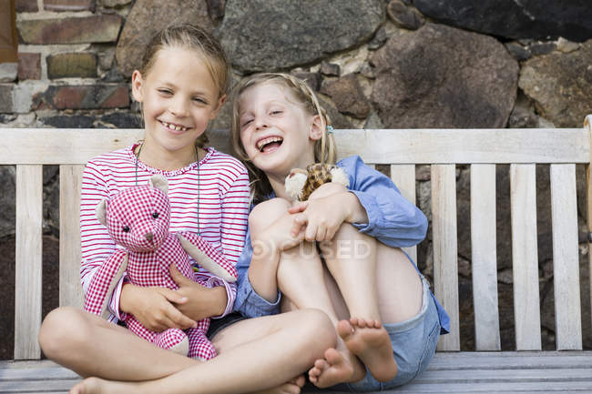 Porträt zweier glücklicher Mädchen, die mit Stofftieren auf einer Bank sitzen — Stockfoto